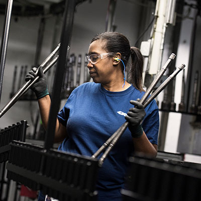 Woman holding steel rods in manufacturing facility