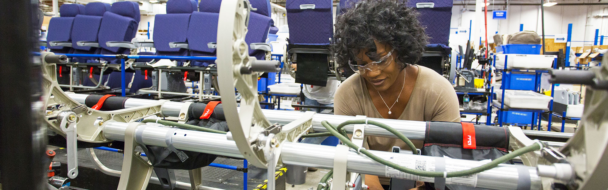 Woman repairing airplane seat in factory