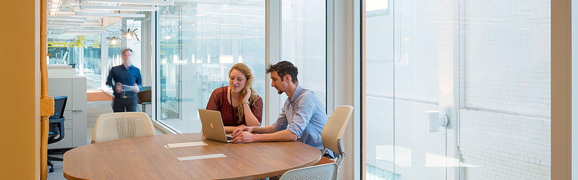 Man and woman collaborating over laptop in office